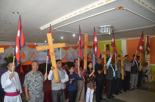 Christians in Nepal rise cross high with the flag of Nepal